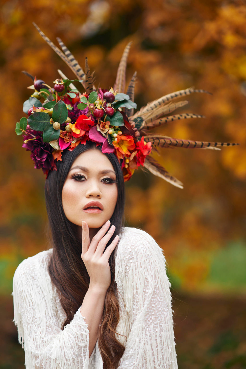 Alternative Christmas Wedding Styled Shoot in reds and golds with large feather headpiece